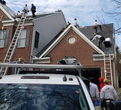 a team of roofers working on a house in Rockville Maryland