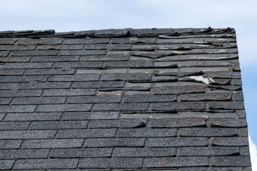 the top corner of a damaged house roof potentially containing asbestos